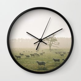 Sunrise burning through heavy fog over field of grazing sheep. Norfolk, UK. Wall Clock