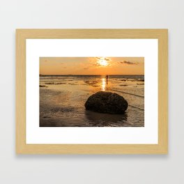 Rock and fisherman silhouette at sunset Framed Art Print