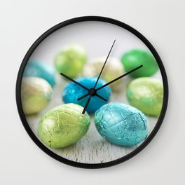 Small chocolate Easter eggs on a rustic white background Wall Clock