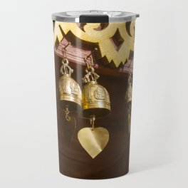 Golden glow on copper bells with clapper hearts, hanging from wooden ceiling. Travel Mug