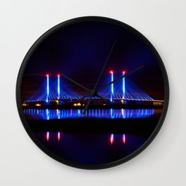 The Indian River Inlet bridge reflecting off the bay as beams of blue light penetrate the night sky Wall Clock
