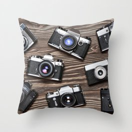 Collection of retro photo cameras on  wood Throw Pillow