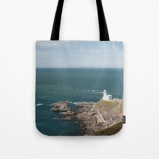 Lighthouse at Hartland Quay with Lundy Island beyond. Devon, UK. Tote Bag