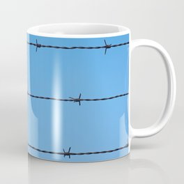 Contseptual shot of barbed wire over blue sky Coffee Mug