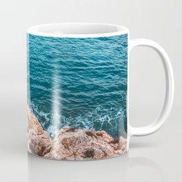 orange rocks in contrast to the blue sea Coffee Mug