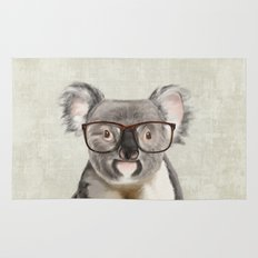 A baby koala with glasses on a rustic background Rug