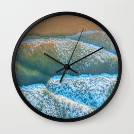 Looking down at ocean waves roll and crash into the shore at sunrise Wall Clock