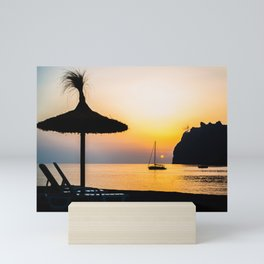 Straw Beach Umbrella and Sailboat Silhouetted at Sunrise on the Mediterranean Mini Art Print