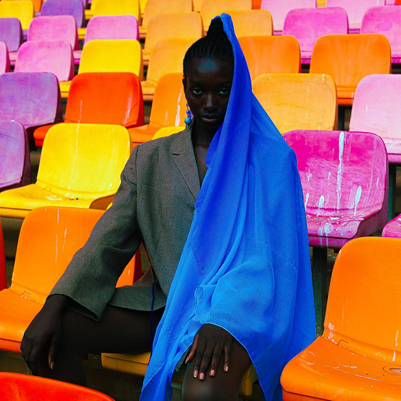 photography of a woman wearing a blue scarf, seated on vivid stadium seats
