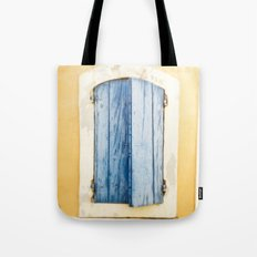Blue wooden shutter in yellow wall. Tote Bag