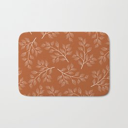 Delicate White Leaves and Branch on a Rust Orange Background Bath Mat