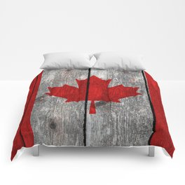 Canada flag on heavily textured woodgrain Comforters