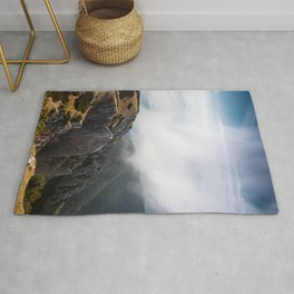 Clouds rolling over mountains Rug