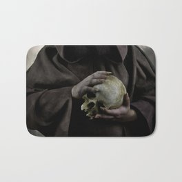 Holding a male skull Bath Mat