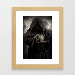 Holding a male skull Framed Art Print