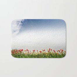 Red and yellow tulips and cloudscape Bath Mat