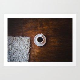 Flatlay brown wood floor and cup of dark coffee next to wool mat Art Print