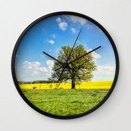 Yellow oilseed rape field under the blue sky with sun Wall Clock