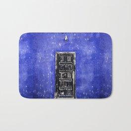 Black worn out door on blue wall Bath Mat