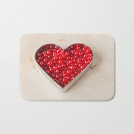 Currants in heart shaped cookie cutter on wood Bath Mat
