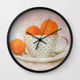 a cup full of apricots Wall Clock