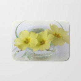 primrose in a coffee cup Bath Mat