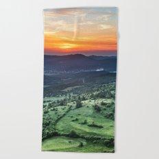 Beautiful sunset behind green fields Beach Towel