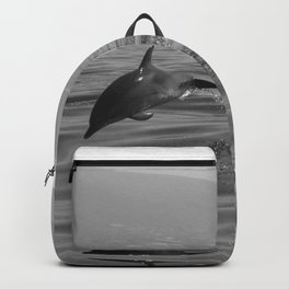 Black and white dolphin race in the ocean Backpack