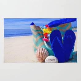 Beach bag with seashell, flip flops, rock and sunscreen by the ocean Rug