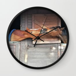 Two brown horses kissing in adjacent boxes Wall Clock