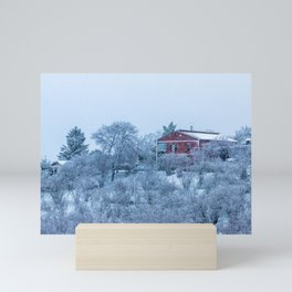 Red house lost in a snowy storm Mini Art Print