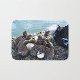 Baby ducks at the shore of the lake Bath Mat