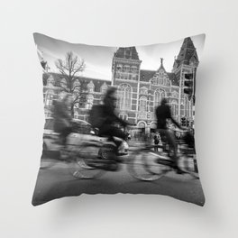Cyclists ride in Amsterdam street in front of the Rijksmuseum Throw Pillow