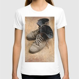 Pair of old leather shoes, worn-out and dusty, on wooden background T-shirt