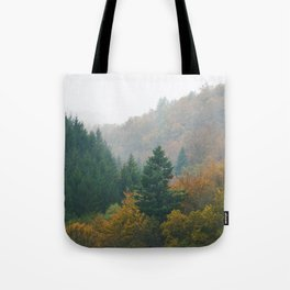 Foggy autumn forest layers disappearing in fog Tote Bag