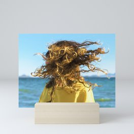 Young bonde woman shakes her curly hair at the beach Mini Art Print