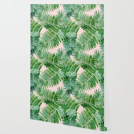 Green palm leaves on a light pink background. Wallpaper
