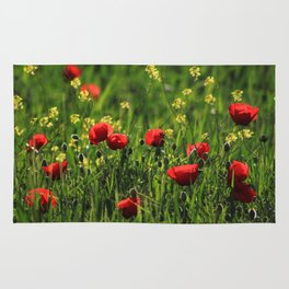 Field with green grass, yellow & red wild flowers in a sunny day Rug