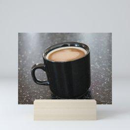 Coffee in a black mug Mini Art Print