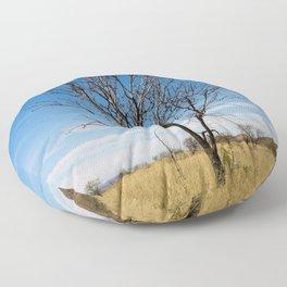 Lone dry tree in serene scene with blue sky Floor Pillow