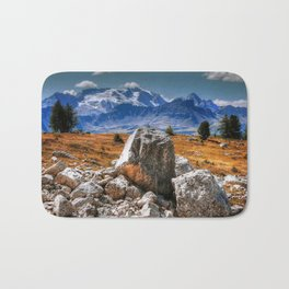 A cropping of dolomitic rocks with a range of mountains in the background Bath Mat