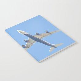 Flying plane enveloped in air Notebook