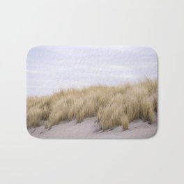 Field of grass growing in the sand Bath Mat