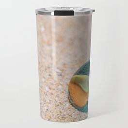 Glass marble with colored interior resting on the sand Travel Mug