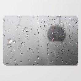 rain drop on cable car window Cutting Board