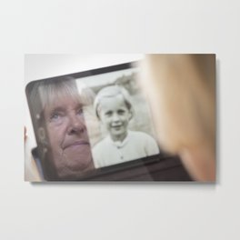 Senior woman looking an image of herself as a child on a tablet computer Metal Print