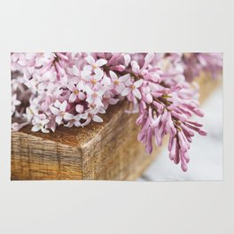Close-up of lilac flowers in a wooden box. Rug