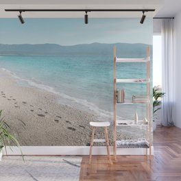 White sandy beach with blue sea, mountains in the back Wall Mural
