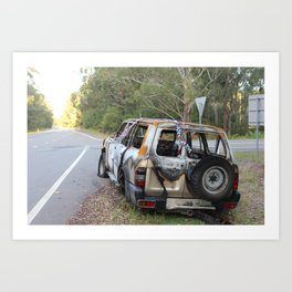 Burnt out car on a deserted road Art Print