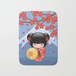 Japanese Red Sakura Kokeshi Doll on Blue Bath Mat